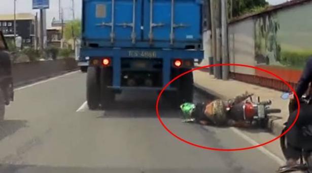 سائق دراجة نارية ينجو بأعجوبة بعد صعود شاحنة فوق رأسه (فيديو)